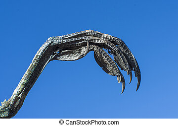 Bird of prey claw on blue sky background