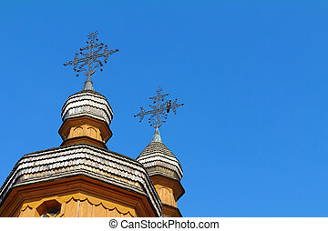 bird on a cross of wooden church