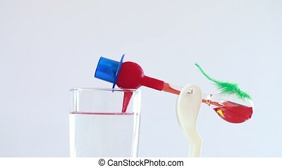 Bird roly-poly drinking water from glass