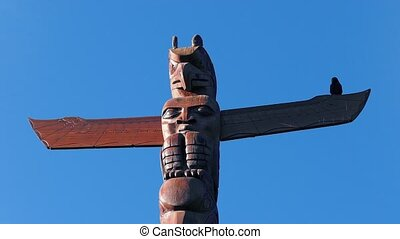 Tribal hand-carved totem pole with a crow sitting on it
