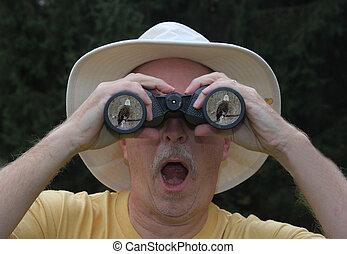 Bird Watcher - Man looking at a Bald Eagle through...
