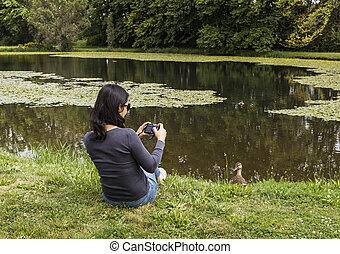 Bird Watching - Mature Asian women taking photos of Mallard...