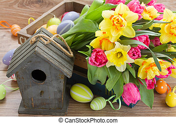 birdcage with spring tulips and daffodils and easter eggs