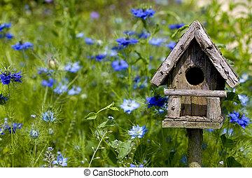 A birdhouse nestles among spring flowers