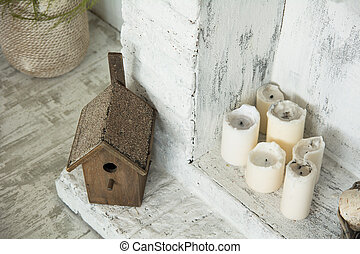 Birdhouse on floor next to the candles