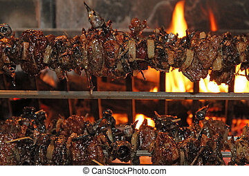 birds and roasts on a spit in the fireplace with the flame lit