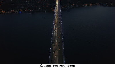 Birds Eye Top Down View of Bridge at Night with Car traffic looking up revealing City Skyline Silhouette, Aerial tilt up