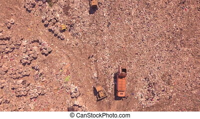 Bird's eye view of a garbage dump where machinery equals mountains of household waste, Ukraine. Ecological problem. High quality FullHD footage