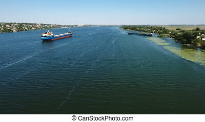 Aerial shot of a large and long barge floating in the middle of the Southern Bug on a sunny day in summer. It leaves a white trail. The drone is flying along it.