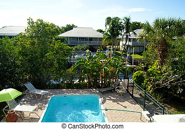 Bird's eye view overlooking swimming pool showing houses and canal with tropical plants.