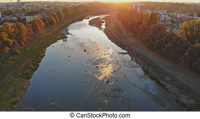 Birds flying over river in during at sunset. Beautiful colorful scenic seagulls over river