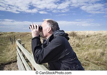 Adult male watching the wildlife through older style black binoculars.