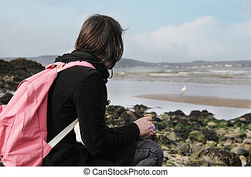 birdwatching - tourist woman watching a great egret on the...