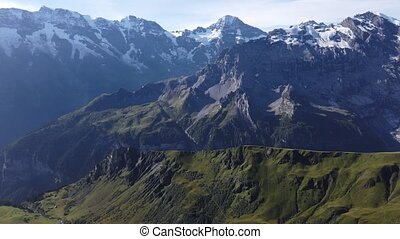 Aerial view above cliffs, rocky mountains and valleys with lakes and rivers at Birg to Schilthorn. Snow-capped peaks of Bernese Prealps, Canton of Bern, Switzerland. Bernese Oberland, Jungfrau Region.