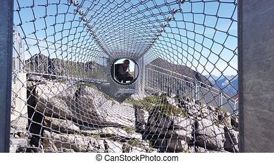 tourist woman on the attraction at the edge of steep cliff in Birg, Switzerland. Tube made of nets of Thrill walk on Schilthorn, Canton of Bern. Swiss family fun outdoor.