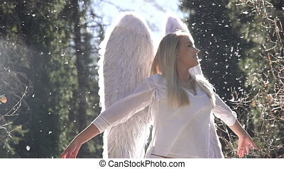 Blonde girl in a white dress with angel wings backlit sunlight. In the air, floating fluff. Motion at a rate of 240 fps