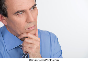 Birth of new business idea. Handsome mature businessman holding his hand on chin and thinking about something while standing isolated on white