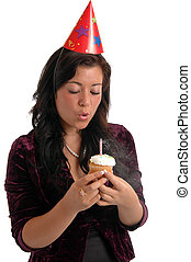 Birthday - A pretty young woman blowing out the candle on a ...