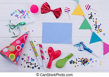 Birthday accessories on white wooden background.