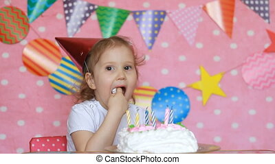 Birthday and party cake. Funny child girl licks her finger with dessert.