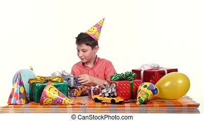 Birthday boy sitting at the table and considers all their gifts, choosing what he likes. slow motion