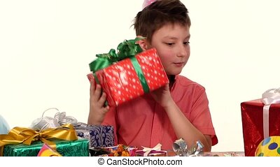 Birthday boy sitting at the table and considers all their gifts, choosing what he likes