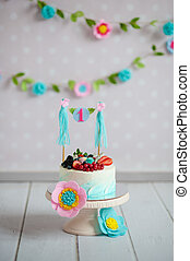 Birthday cake decorated with fruits and a garland with the...