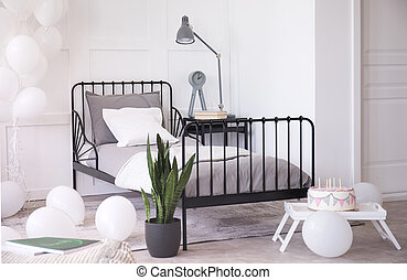 Birthday cake with candles, green plant in black pot and white balloons in bright elegant bedroom interior, real photo