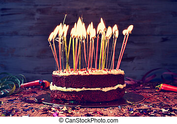 birthday cake with some lit candles, filtered
