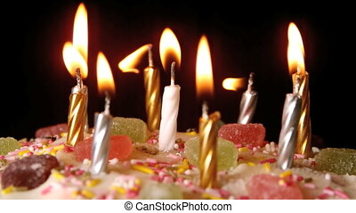 Birthday candles being blown out on a delicious cake close...