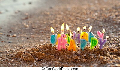 Birthday candles burning on a seashore