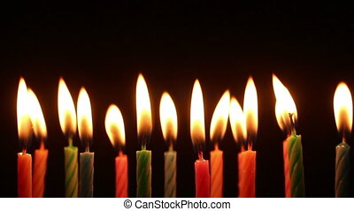 birthday candles light on isolated black