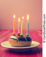Birthday candles on a donut - Colorful birthday candles with...