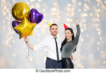 happy couple in party hats with balloons