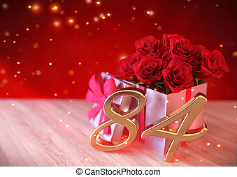 birthday concept with red roses in gift on wooden desk. eighty-fourth. 84th. 3D render