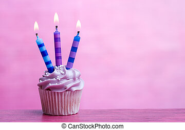 Cupcake decorated with three birthday candles