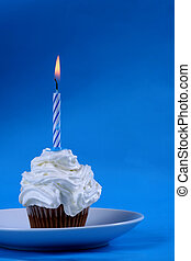 Birthday cupcake with a single candle on it on blue...