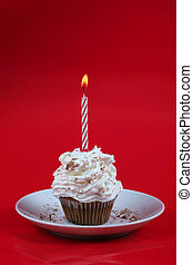 Birthday cupcake with a single candle on it on red ...
