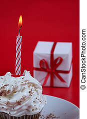 Birthday cupcake with a single candle on it on red...