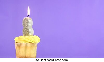 Birthday cupcake with candle number eight.