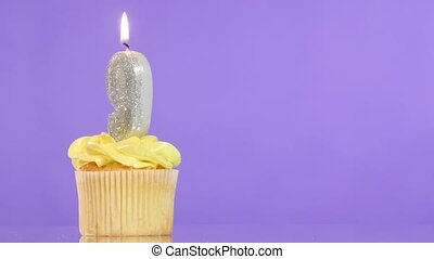 Birthday cupcake with candle number nine.