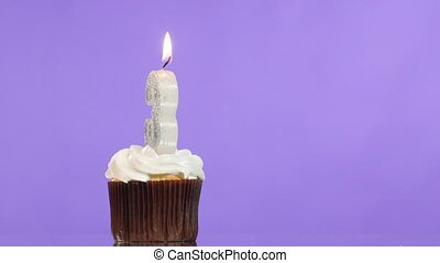 Birthday cupcake with candle number three.