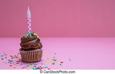Birthday cupcake with candle on pink pastel background, copy space.