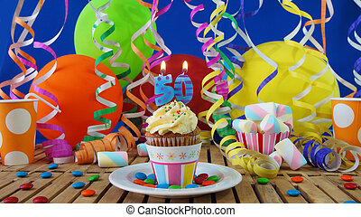 Birthday cupcake with candles burning on rustic wooden table...