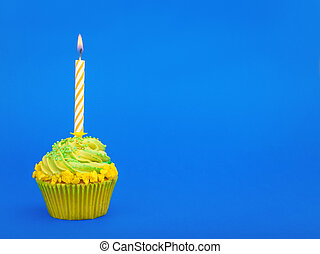 birthday cupcake with candles on blue background