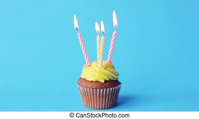 birthday cupcake with four burning candles