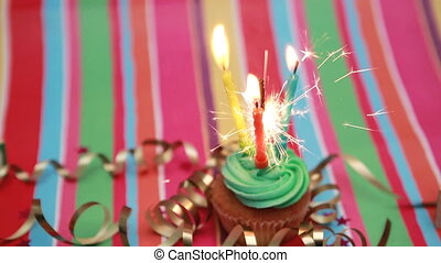 Birthday cupcake with sparkler and candle on rainbow...
