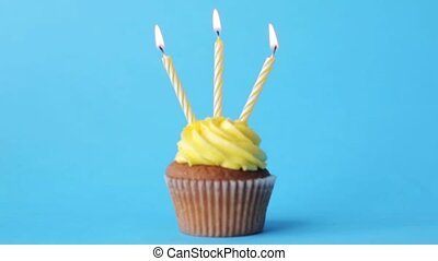 birthday cupcake with three burning candles