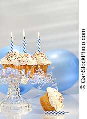 Birthday cupcakes with blue candles and balloons