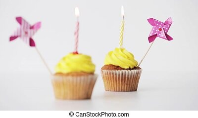 birthday cupcakes with burning candle and pinwheel